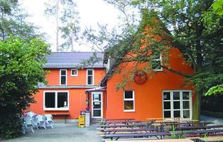 Das Bild zeigt das Haus und den Sitzbereich davor.