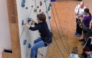 eine Frau klettert an der Kletterwand und wird dabei gesichert