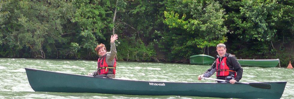 Touring-Boot der NaturFreunde mit zwei Fahrern, Frau winkend